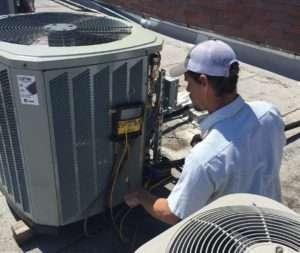 Custom Services heat and air technician repairing a unit jenks oklahoma.